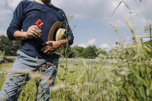 Man with hat holding flower while standing in field during sunny day - GUSF04413