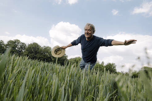Confident smiling man holding hat while balancing against cloudy sky in field - GUSF04431