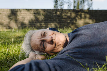 Confident smiling man lying in field - GUSF04434