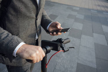 Midsection of male commuter using smart phone while holding electric push scooter handle - VPIF02951