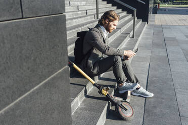 Male commuter using digital tablet while sitting with electric push scooter on steps at downtown - VPIF02969
