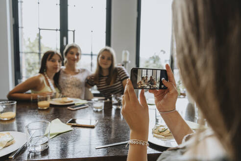 Group of teenage girls meeting for brunch, taking smartphone pictures - MFF05997