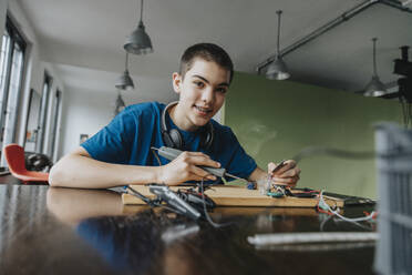 Boy sitting at home using soldering iron - MFF06057