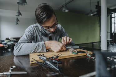 Young man tinkering with soldering iron at home - MFF06060