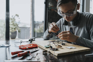 Young man tinkering with soldering iron at home - MFF06063