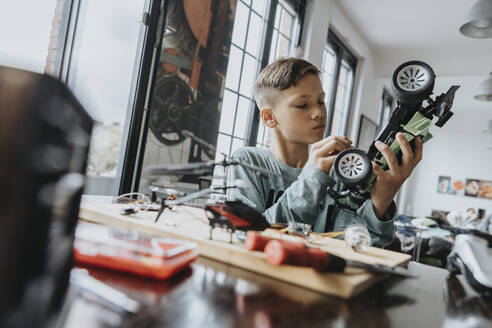 Boy assembling on remote-controlled toy car with screwdriver - MFF06072
