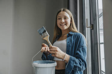 Smiling teenage girl standing in room, holding paint bucket and brush - MFF06084