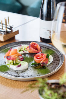 Salmon rolls with onion and herbs served on metal plate on wooden table with glass and bottle of white wine - ADSF11750