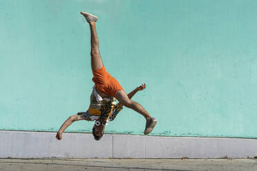 Casual man somersaulting in front of green wall - AFVF06995