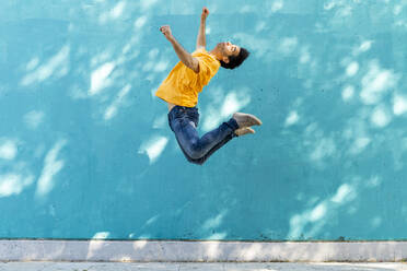 Casual man jumping in front of blue wall - AFVF07007