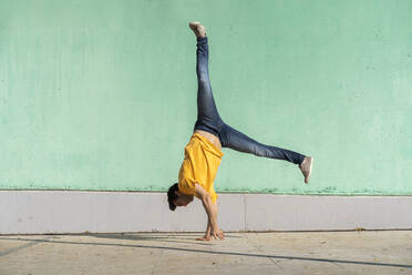 Casual man doing handspring in front of green wall - AFVF07010