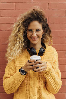 Smiling beautiful young woman with long curly blond hair holding disposable coffee cup against red brick wall - BOYF01363