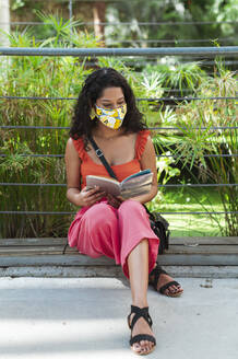 Young woman wearing protective mask while reading book sitting in park during COVID-19 pandemic - JMPF00353
