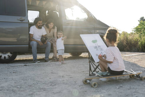 Girl painting while parents in van with baby sister at park during sunset - JCZF00191