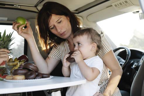 Beautiful woman looking at daughter eating donut while sitting in van during sunset - JCZF00206