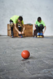 Close-up of red hockey ball on floor against father and son wearing roller skates at court - VEGF02823