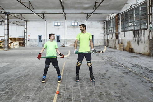 Mature man and his son holding hockey sticks while looking at each other - VEGF02829