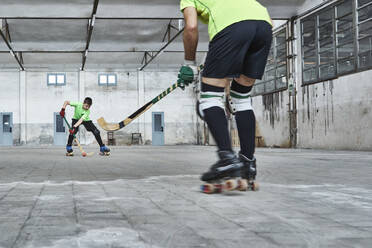 Father and son playing roller hockey on court - VEGF02832