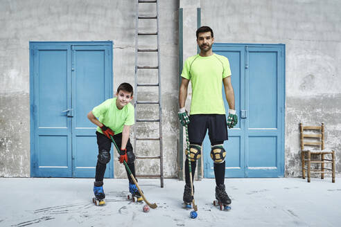 Mature man and his son holding hockey sticks against doors at court - VEGF02835