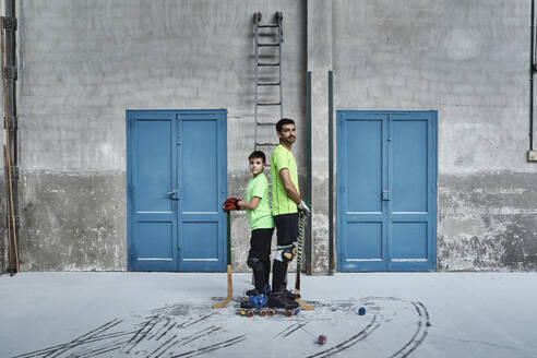 Father and son standing back to back while holding hockey sticks by doors at court - VEGF02838