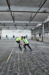 Father teaching son playing roller hockey on court - VEGF02841