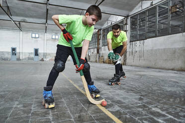 Boy practicing roller hockey with father on court - VEGF02844
