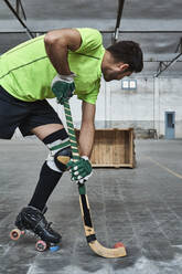 Mature male athlete practicing roller hockey while aiming at wooden box - VEGF02847