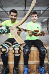 Close-up of hockey sticks held by father and son sitting on wooden box at court - VEGF02850