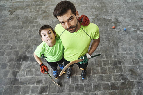 Boy with arm around father holding sticks at hockey court - VEGF02853