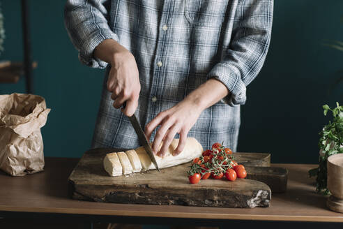 Midsection of man cutting fresh homemade bread by cherry tomatoes on board in kitchen - ALBF01404