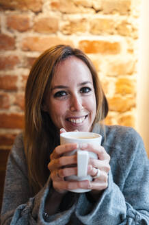Woman smiling while holding coffee cup against brick wall at coffee shop - JMPF00355