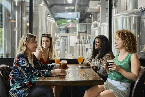 Female friends socializing in a pub - ZEDF03636