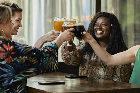 Happy female friends clinking craft beer glasses in a pub - ZEDF03639