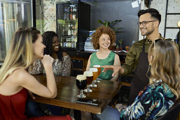 Waiter serving craft beer for female friends in a pub - ZEDF03642