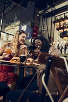 Happy female friends with smartphone having burgers in a pub - ZEDF03660