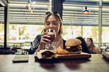 Woman having a beer and a burger in a pub - ZEDF03663