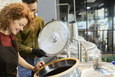 Man and woman working in craft brewery looking into tank - ZEDF03696