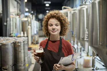 Portrait of confident woman holding clipboard and beer glass in craft brewery - ZEDF03711