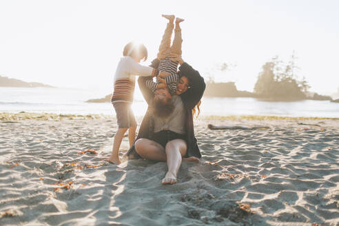 Mother playing with children while sitting on sand at beach - CMSF00123