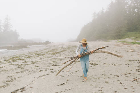 Woman wearing hat carrying logs while walking at beach - CMSF00129