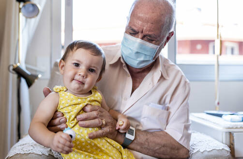 Grandfather with protective mask and baby girl at home - GEMF04093