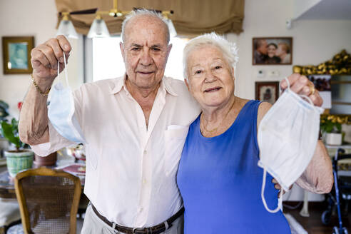 Senior couple holding protective masks at home - GEMF04099