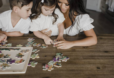 Smiling mother solving puzzle with kids over table at home - SMSF00207