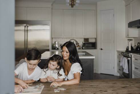 Smiling parents solving puzzle with children over table at home - SMSF00210