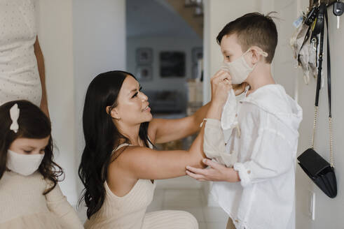 Mother covering son's face with protective mask at home during COVID-19 - SMSF00225