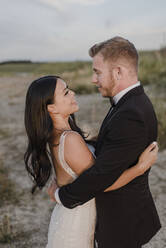 Smiling bridegroom looking at each other in field - SMSF00249
