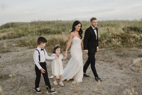 Parents with children wearing wedding dress while walking in field - SMSF00252