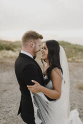 Smiling bridegroom looking at each other in field against sky - SMSF00255