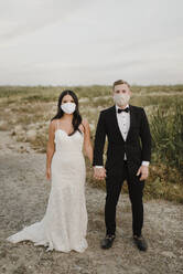 Bride and groom with protective face mask standing in field during COVID-19 - SMSF00267