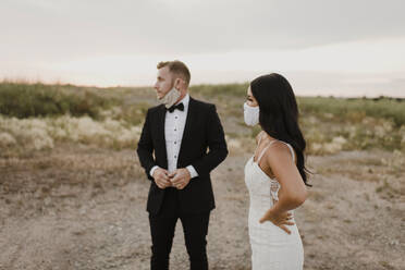 Bride with groom wearing protective face mask while looking away in field during COVID-19 - SMSF00270